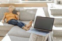 Ordenador portátil en el sofá en la habitación - foto de stock