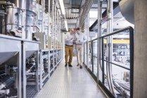 Uomini discutere prodotto in fabbrica — Foto stock