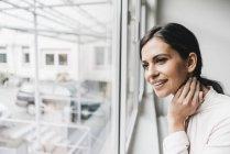 Жінка дивиться з вікна — стокове фото