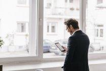 Uomo d'affari utilizzando tablet accanto alla finestra — Foto stock