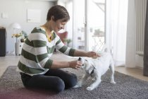 Женщина сидит на полу и играет с собакой — стоковое фото