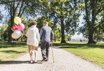 Couple de personnes âgées avec des ballons se promener — Photo de stock