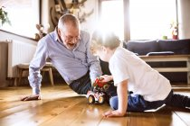 Grandfather and grandson playing with toys — Stock Photo