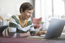 Donna sdraiata sul pavimento e utilizzando il computer portatile — Foto stock