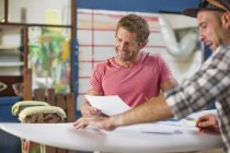 Men with surfboard and documents — Stock Photo