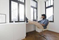 Man sitting in minimalist empty room — Stock Photo