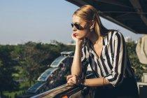 Mujer joven con estilo disfrutando de la luz del sol - foto de stock
