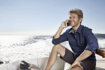 Man talking by phone on motor yacht — Stock Photo