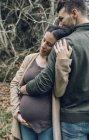 Чоловік, який обіймає вагітну жінку — стокове фото