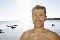 Smiling man in front of sea — Stock Photo