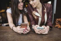 Two young women using cell phones in a bar — Stock Photo