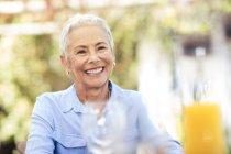 Retrato de mujer mayor sonriente al aire libre - foto de stock