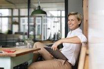 Glücklich blonde Frau mit Tablet am Tisch sitzen — Stockfoto
