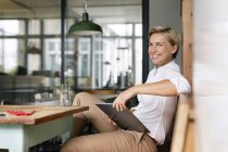 Happy blond woman with tablet sitting at table — Stock Photo