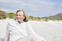 Femme assise sur la plage — Photo de stock