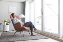 Woman relaxing on armchair — Stock Photo