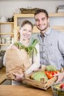Couple with box of vegetables in kitchen — Stock Photo