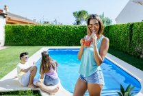 Woman holding drink at poolside — Stock Photo