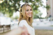 Mulher loira sorridente com fones de ouvido — Fotografia de Stock