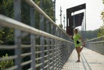 Female athlete stretching on bridge — Stock Photo