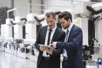 Businessmen sharing tablet — Stock Photo