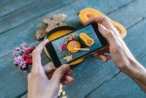 Hands taking photos of creamed pumpkin — Stock Photo