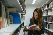 Schüler lesen Buch in Bibliothek — Stockfoto