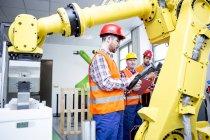 Trois hommes en usine avec robot industriel — Photo de stock
