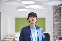 Homme debout dans le bureau avec les yeux fermés — Photo de stock
