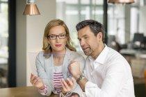 Homme d'affaires et de la femme à l'aide de dispositif portatif — Photo de stock