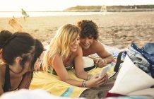 Чоловік і жінка, спільного використання стільникового телефону на пляжі — стокове фото