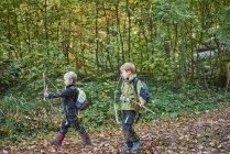 Два хлопчика, проходячи через ліс з Луки і стріли — стокове фото