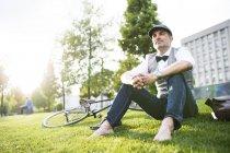 Бизнесмен с велосипедом сидит на траве — стоковое фото