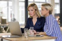Due donne che utilizzano il computer portatile — Foto stock