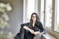 Femme à lunettes, assis à la fenêtre — Photo de stock