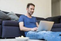 Hombre sentado en el suelo y el uso de ordenador portátil - foto de stock