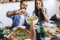 Amigos comiendo papas fritas y pizza - foto de stock