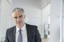 Imprenditore in piedi in ufficio — Foto stock