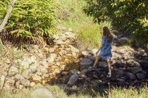 Mujer caminando cerca de arroyo de la montaña - foto de stock