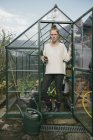Woman standing in greenhouse — Stock Photo