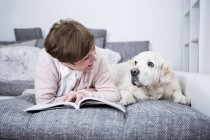 Senior woman lying on couch with dog — Stock Photo