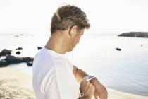 Мужчина с наушниками проверяет свой смартфон — стоковое фото