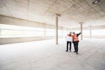 Men interacting in building under construction — Stock Photo