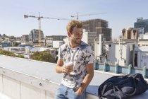 Чоловік п'є каву на терасі на даху — стокове фото