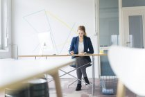 Businesswoman working at desk — Stock Photo