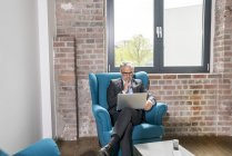 Businessman sitting in armchair and using laptop — Stock Photo