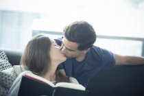 Man kissing girlfriend with book — Stock Photo