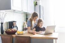 Mãe e filha usando laptop na cozinha — Fotografia de Stock