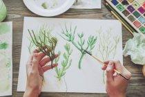 Woman painting plants — Stock Photo