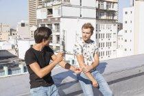 Friends talking on a rooftop terrace — Stock Photo